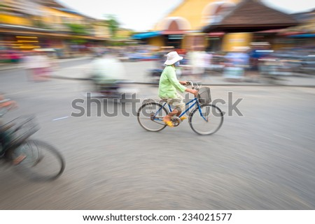Asian woman riding blue bike. Person on bicycle. Crossroad of Hoi An in Vietnam, Asia. Blur motion of busy street with houses and transport. Famous destination for tourists. Eastern city life. - stock photo