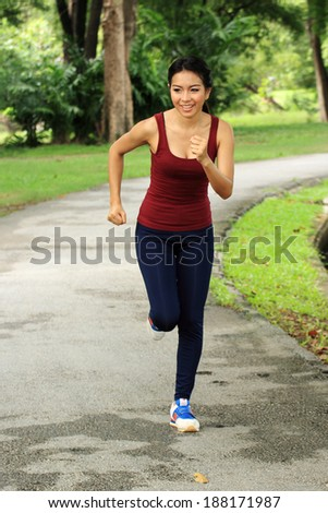 Asian woman running in park in sunshine on the holiday - stock photo