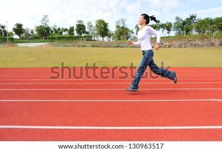 asian woman running on tracks - stock photo