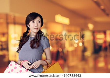 Asian woman shopping and looking at modern mall with copyspace. - stock photo
