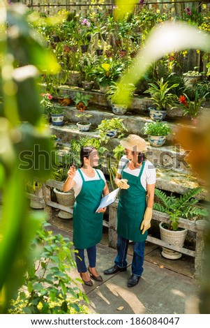 Asian woman showing to man new sorts of plants in the greenhouse - stock photo