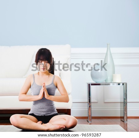 Asian woman sitting on a yoga mat doing the salutation seal pose. Meditation. - stock photo
