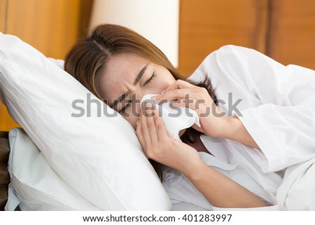 Asian woman sneezing in a tissue on bed - stock photo