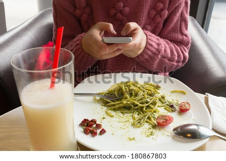 Asian woman text messaging during  meal in a restaurant - stock photo