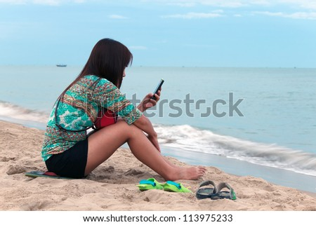 Asian woman use mobile phone on the beach. - stock photo