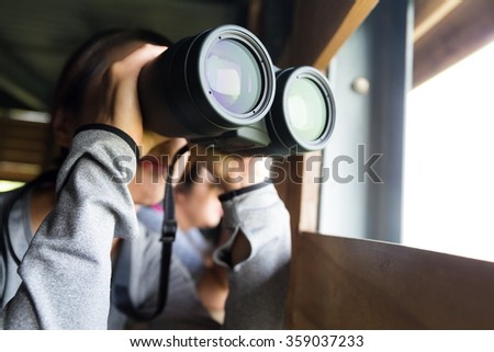 Asian Woman use of the binoculars at wooden house  - stock photo