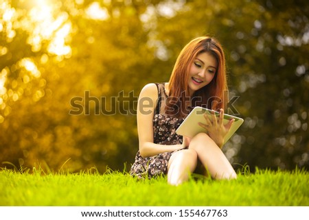 Asian woman using digital tablet in park, Outdoor Portrait - stock photo