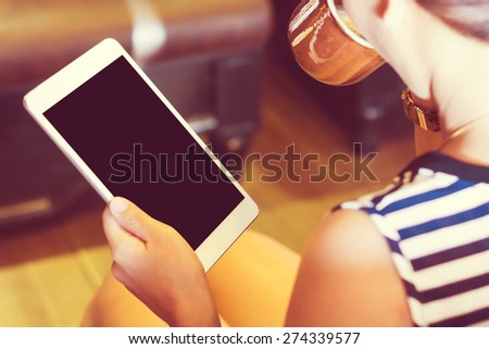 Asian woman using tablet computer in cafe drinking coffee. Focus on tablet. (Vintage process tone) - stock photo