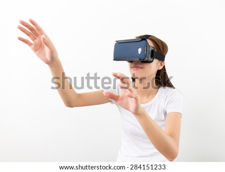 Asian woman using the virtual reality headset and two hand touch on air - stock photo
