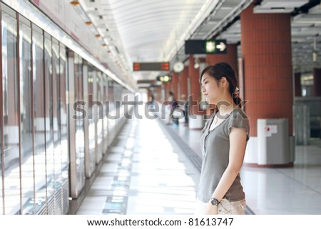 Asian woman waiting for train - stock photo