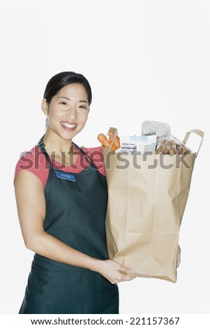 Asian woman wearing apron and holding grocery bag - stock photo
