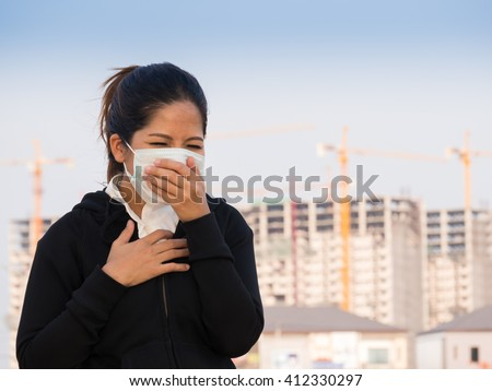 asian woman wearing face mask with construction background - stock photo