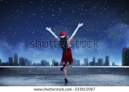 Asian woman wearing santa claus costume, standing on the rooftop, looking the city - stock photo