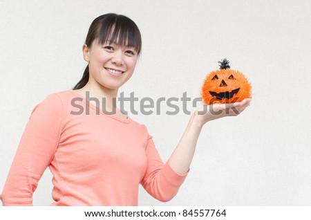 Asian woman with a Halloween pumpkin - stock photo