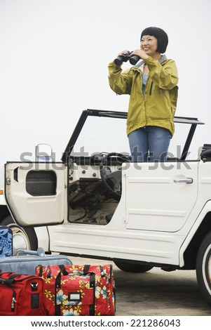 Asian woman with binoculars in convertible - stock photo