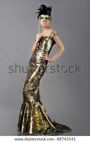 Asian woman with carnival mask in golden dress - stock photo