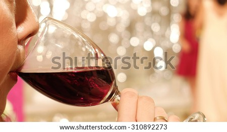 Asian Woman with Lipstick Sipping Red Wine in a Glass at The Corner with Blur Celebration Party in Background - stock photo