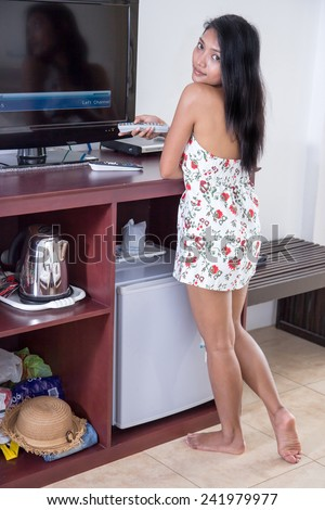 Asian woman with remote control switching channels on tv - stock photo