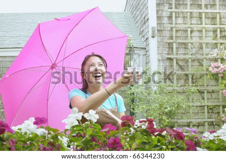 Asian woman with umbrella holding mug out in rain - stock photo