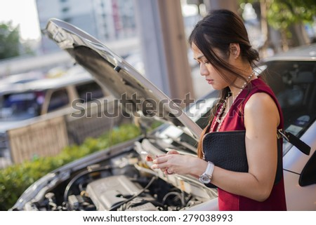 Asian women broken car and call the repairman on a working day. - stock photo