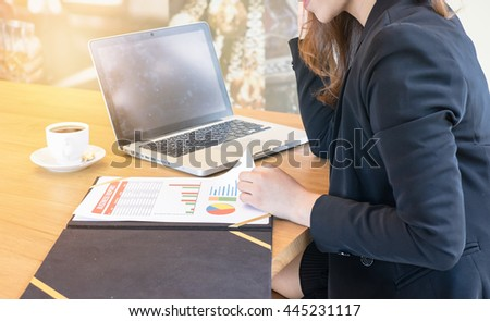Asian women Businesswoman Analyzing Graph While Laptop On Office Desk .close up of business woman hand working on laptop computer with business graph information diagram on office desk   - stock photo