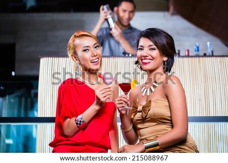 Asian women drinking cocktails in fancy bar - stock photo