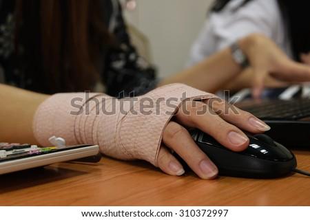 Asian women hand sore working on her computer - stock photo