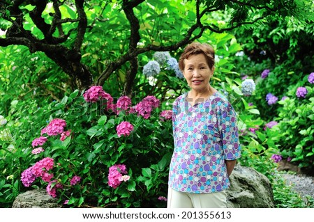 Asian women in senior standing in the garden of green - stock photo