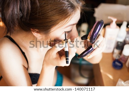 asian women make up her face in room - stock photo