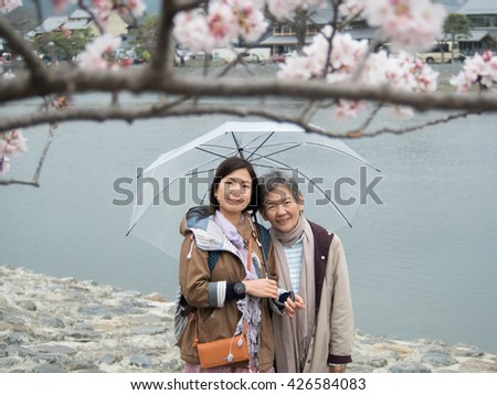 Asian women portrait - Senior mother and adult daughter with umbrella looking to the camera at Nishikyo-ku, Kyoto, Japan - stock photo