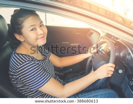 Asian women smiling and happy while driving her modern car in a city. - vintage style color effect - stock photo