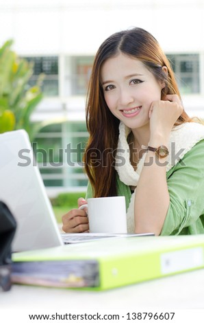 Asian women student looking and smiling with coffee cup - stock photo