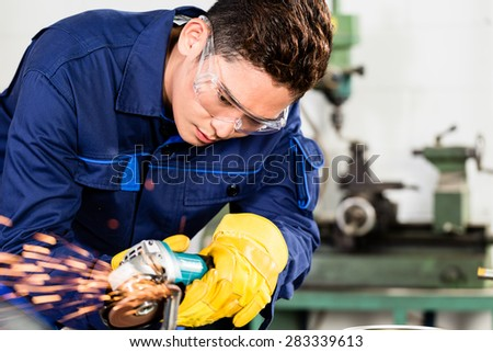 Asian worker grinding metal in manufacturing plant, sparks flying as he is working on the piece - stock photo
