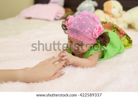 Asian young baby play with mother hand. - stock photo