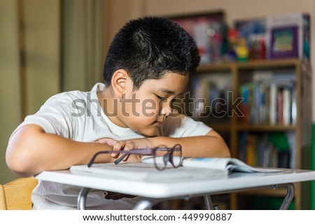 Asian Young boy doing homework - stock photo