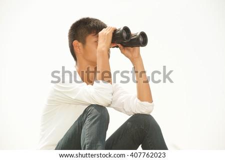 Asian young boy sit is seeking binoculars . - stock photo
