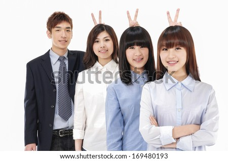asian young business partners looking at camera with smiles and showing sign of victory - stock photo