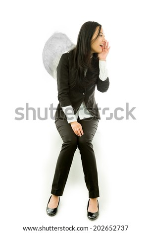 Asian young businesswoman sitting on stool dressed up as an angel whispering message isolated on white background - stock photo