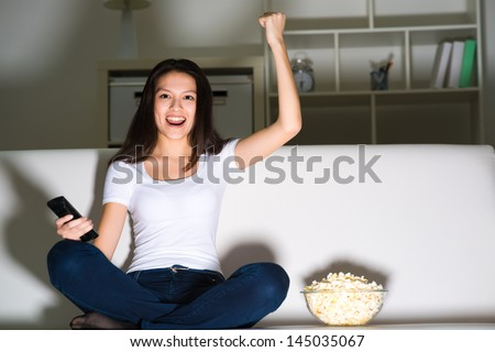 Asian young girl with excitement at night watching TV in the living room - stock photo