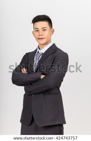 asian young handsome businessman standing arms crossed, looking at camera. - stock photo