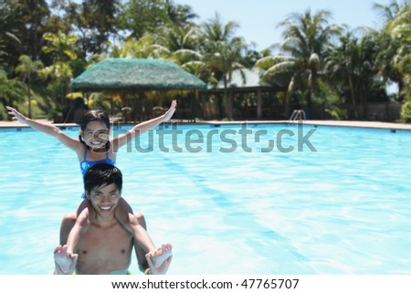 asian young man and a child enjoying on a swimming pool - stock photo