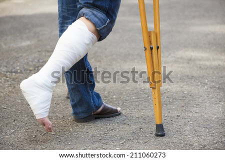 asian Young man on crutches with tree background - stock photo