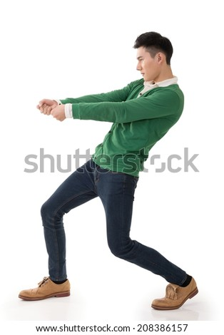 Asian young man posing tug of war, full length portrait isolated on white. - stock photo