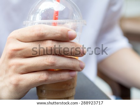 Asian young man using a straw to drink from a plastic cup. - stock photo