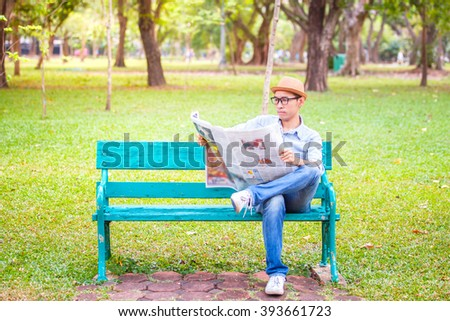 Asian young Man with hat sitting on a wooden bench and reading a newspaper in a park - stock photo