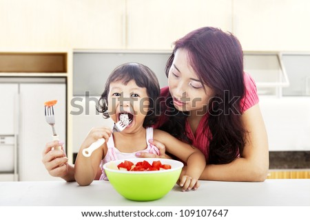 Asian young mother helping her daughter eats fresh fruit salad. shot in the kitchen - stock photo