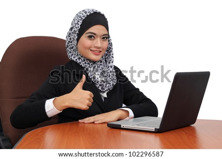 Asian young muslim businesswoman holding a laptop with thumb up against white background - stock photo