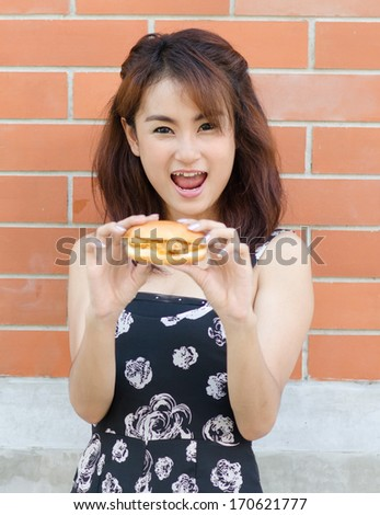 Asian young woman eat  tasty fast food (chicken burger) unhealthy burger in hand hungry getting ready to eat - stock photo