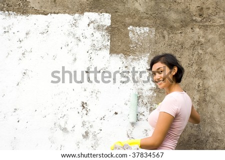 Asian young woman enjoy painting her house with white paint - stock photo