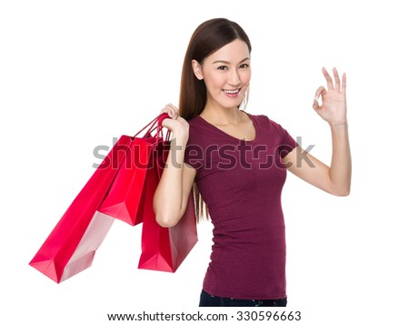 Asian Young Woman hold with shopping bag and ok sign gesture - stock photo